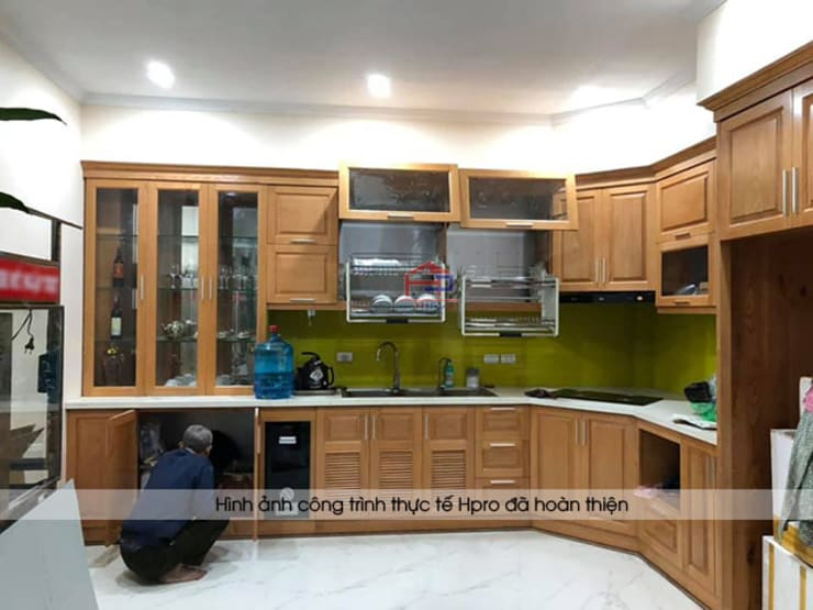 Ảnh thực tế mặt đá bàn bếp marble và kính ốp bếp màu vàng chanh trong bộ tủ bếp gỗ sồi mỹ nhà anh Lệ ở Minh Khai:  Kitchen by Nội thất Hpro
