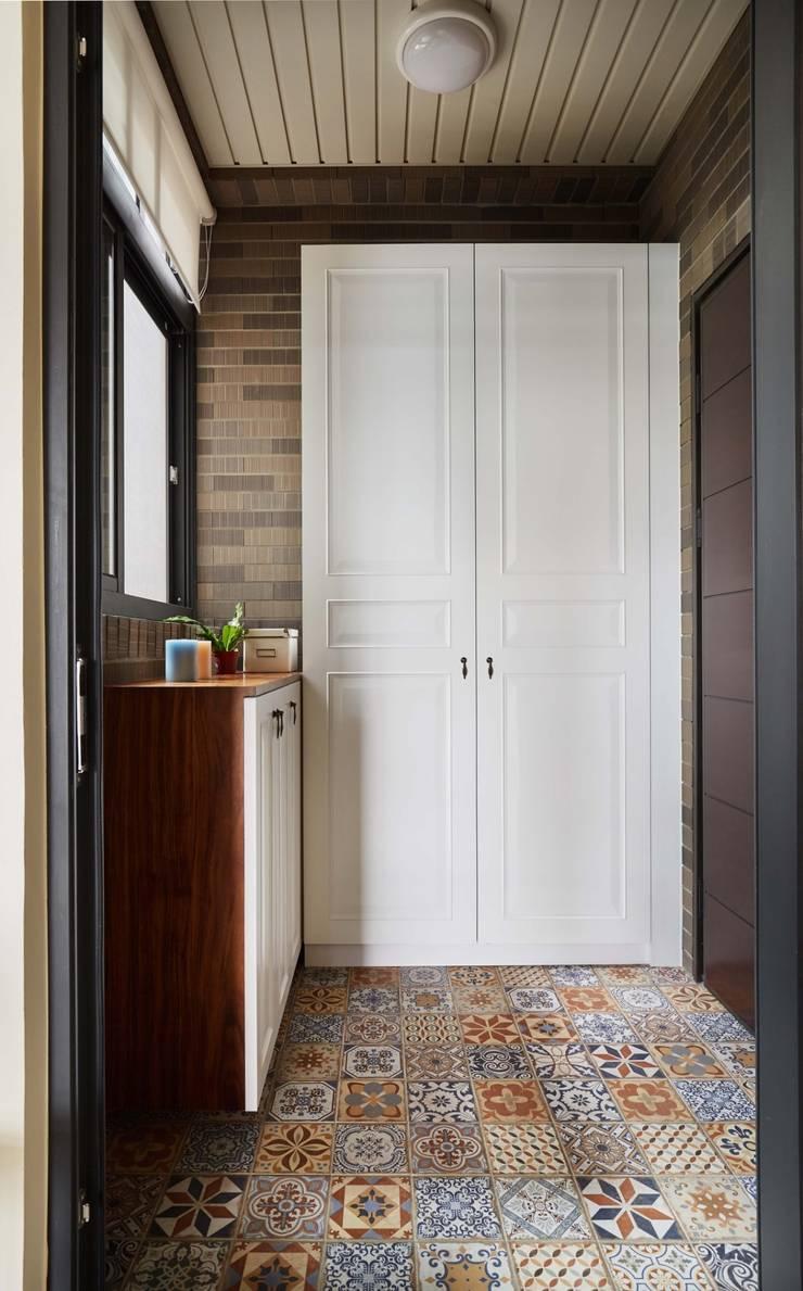 一進門的右手邊設置大型收納櫃,地面則用花磚與室內做區隔:  牆壁與地板 by 弘悅國際室內裝修有限公司