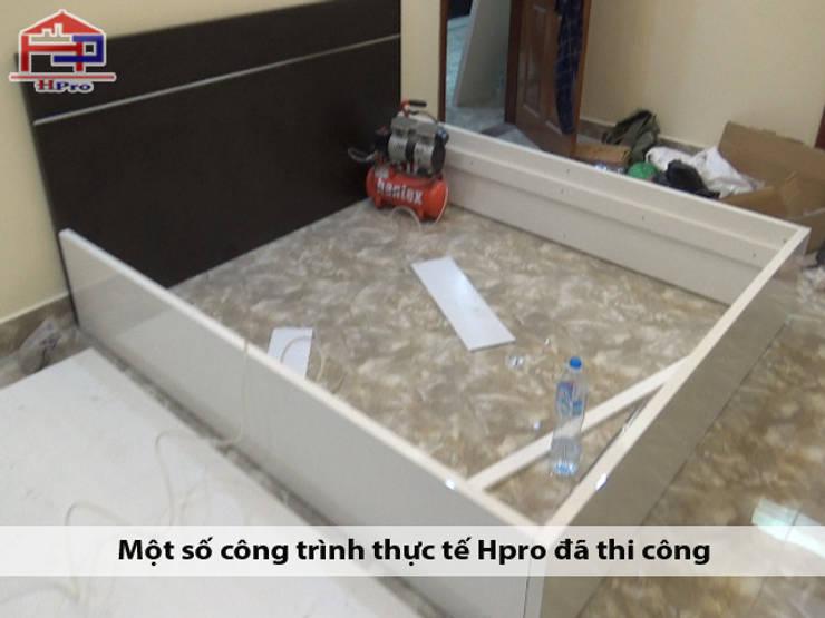 Lắp đặt giường ngủ melamine trong nội thất phòng ngủ master nhà chị Ngọc ở Chùa Láng:  Bedroom by Nội thất Hpro