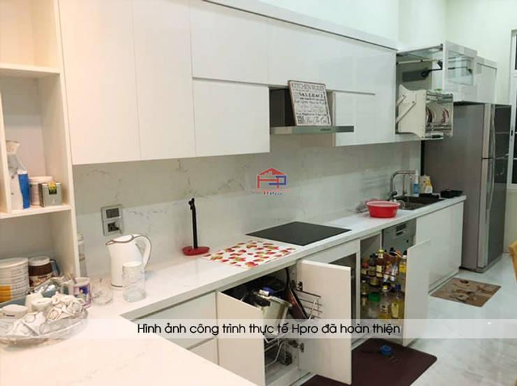 Ảnh thực tế tủ bếp acrylic màu trắng sau khi được lắp ráp đầy đủ phụ kiện và thiết bị nhà chị Thu ở Long Biên:  Kitchen by Nội thất Hpro