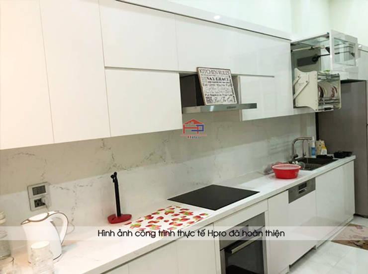 Ảnh thực tế tủ bếp acrylic màu trắng cùng mặt đá bàn bếp marble vân mây nhà chị Thu ở Long Biên:  Kitchen by Nội thất Hpro