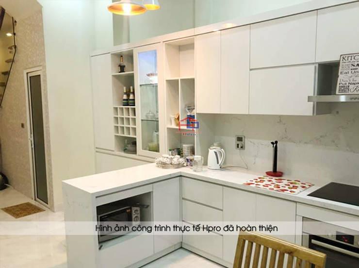 Ảnh thực tế tủ bếp acrylic kèm bàn đảo và tủ rượu nhà chị Thu ở Long Biên:  Kitchen by Nội thất Hpro