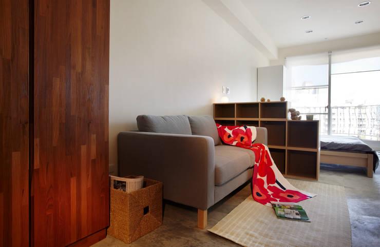 利用櫃子將客廳與睡眠區隔開:  客廳 by 弘悅國際室內裝修有限公司
