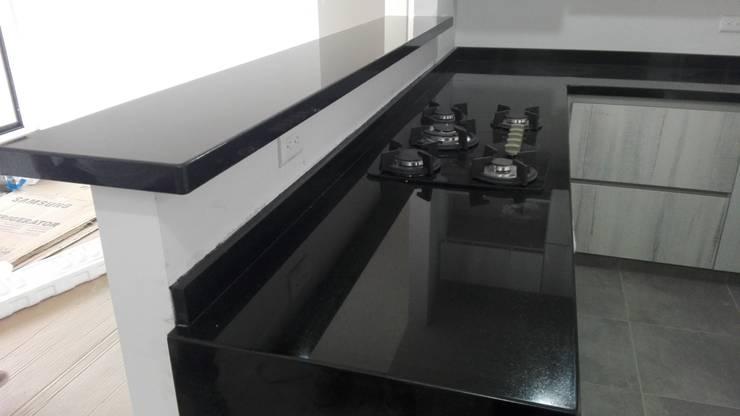 barra y meson con estufa en granito negro absoluto: Cocinas integrales de estilo  por planet stone sas, Moderno Granito