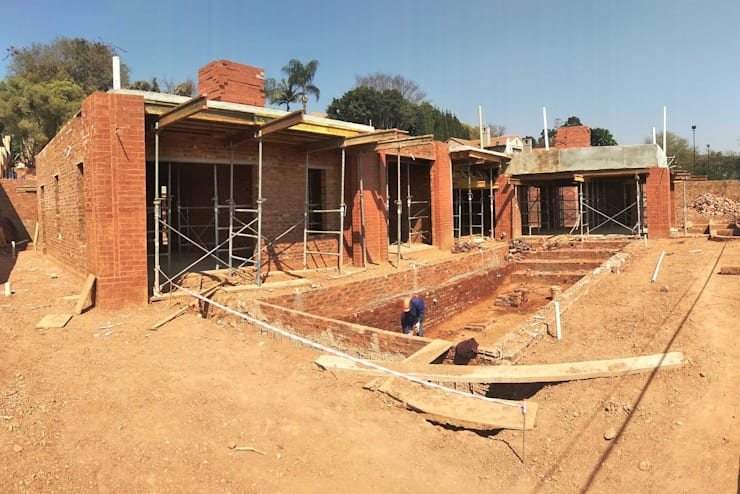 construction of swimming pool area:  Houses by Nuclei Lifestyle Design