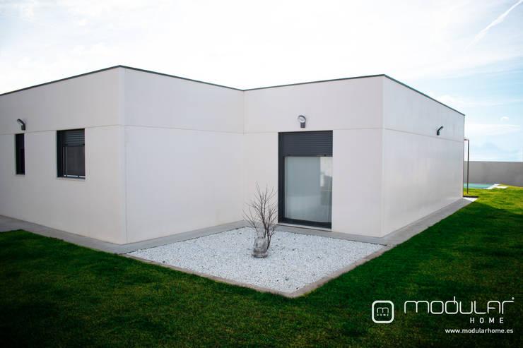 Patio trasero de grava blanca: Casas prefabricadas de estilo  de MODULAR HOME,