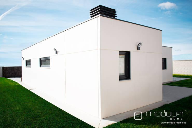 Fachada trasera de vivienda prefabricada de hormigón: Casas prefabricadas de estilo  de MODULAR HOME,