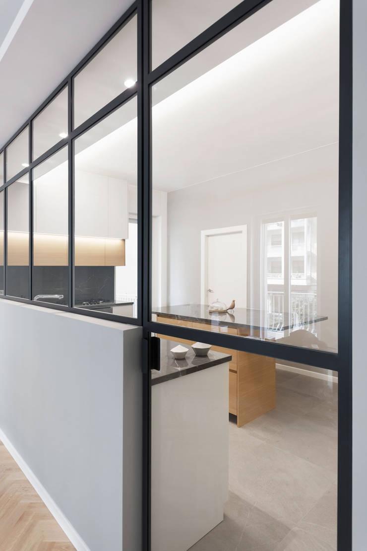 Porta e vetro integrata in vetrata verso la cucina: Cucina attrezzata in stile  di PLUS ULTRA studio,