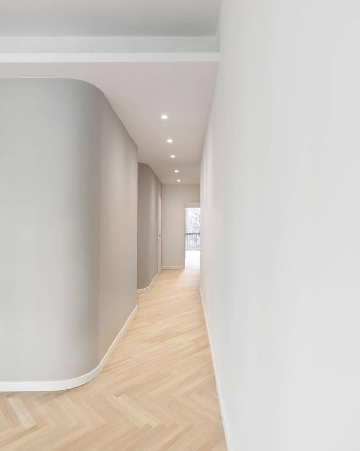 Disimpegno tra zona giorno e zona notte con angoli arrotondati e pavimento in parquet di rovere: Ingresso & Corridoio in stile  di PLUS ULTRA studio,