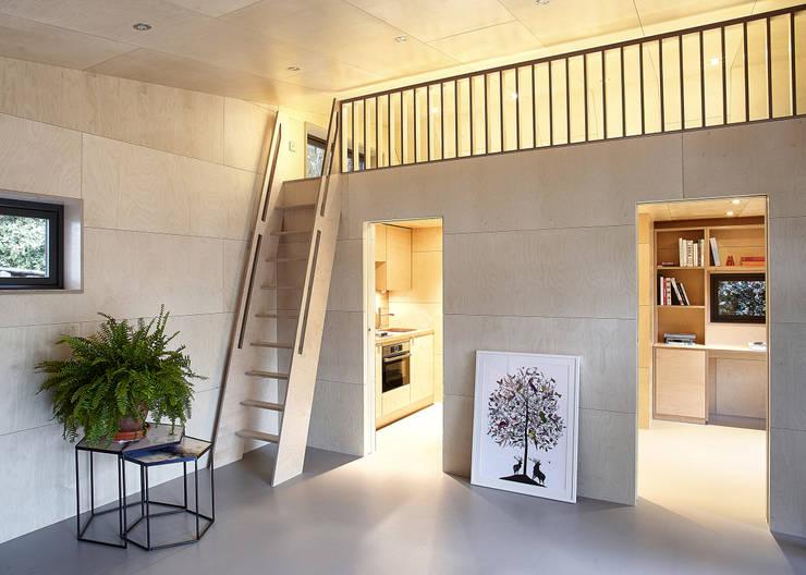 Vista del soggiorno con la scala di accesso al mezzanino: Soggiorno in stile  di Ecospace Italia srl