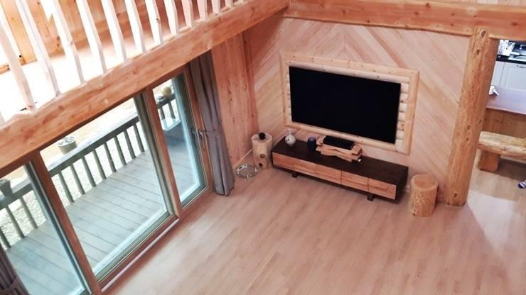 웅장한 통나무기둥이 공간을 드라마틱하게 -순천 마륜리 하이브리드 통나무집: 보국주택의  ,