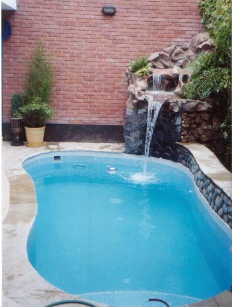Piscina con caída de agua: Piscinas de estilo  por PISCINES