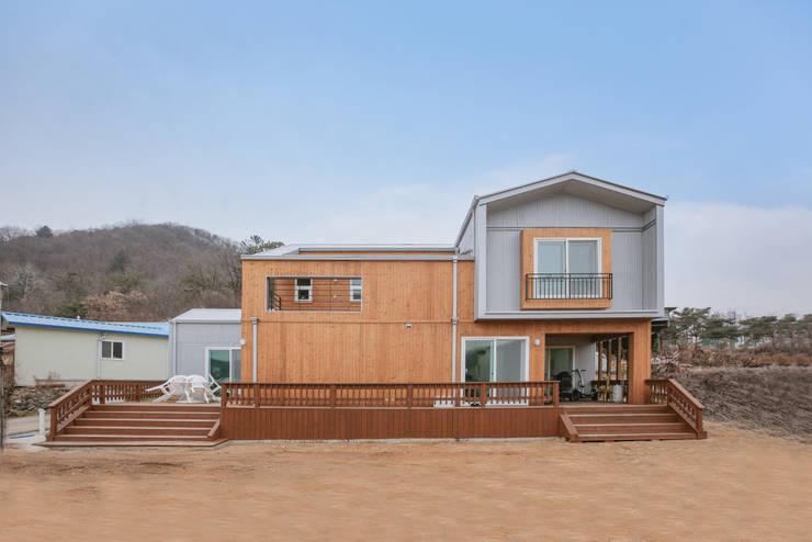 푸른 산이 감싸는 전원주택: 공간제작소(주)의  목조 주택,