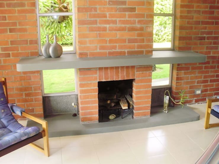 Chimenea Sala Salones de estilo tropical de DESIGNIO Arquitectura + Objetos Tropical Ladrillos