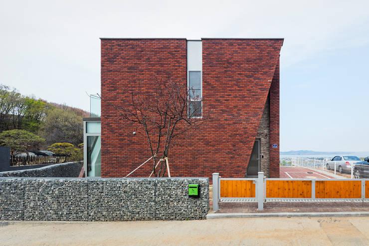 붉은 벽돌의 외관: 큐제이아키텍쳐 QJARCHITECTURE의  전원 주택,