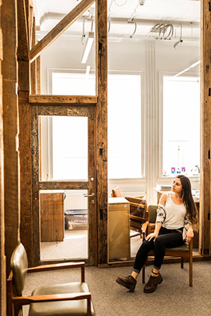 Oficina con madera recuperada y vidrio laminado. : Centros de exhibiciones de estilo  por Intarq SpA