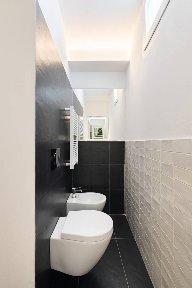 Bagno con pavimento in gres nero: Bagno in stile  di B+P architetti