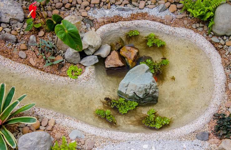 Poseta  con cascada al interior: Jardines de piedra de estilo  por Juan Sebastián Jaramillo Lizarralde,