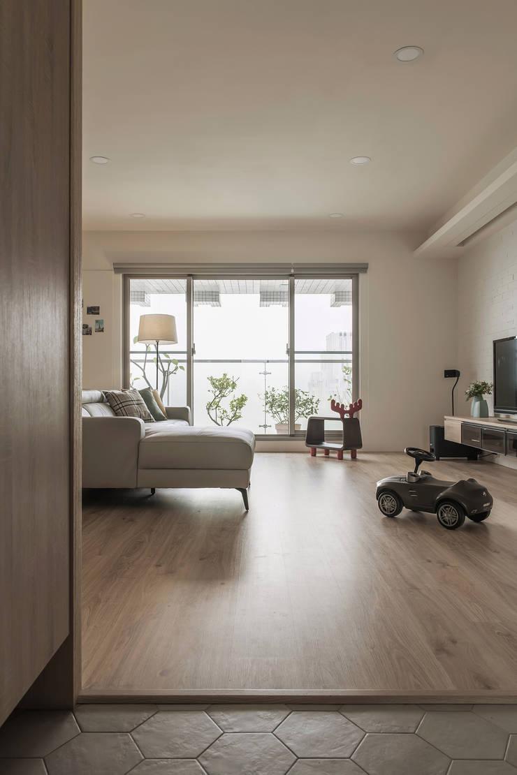 大片落地窗通往陽台並讓室內充滿自然光:  客廳 by 詩賦室內設計,
