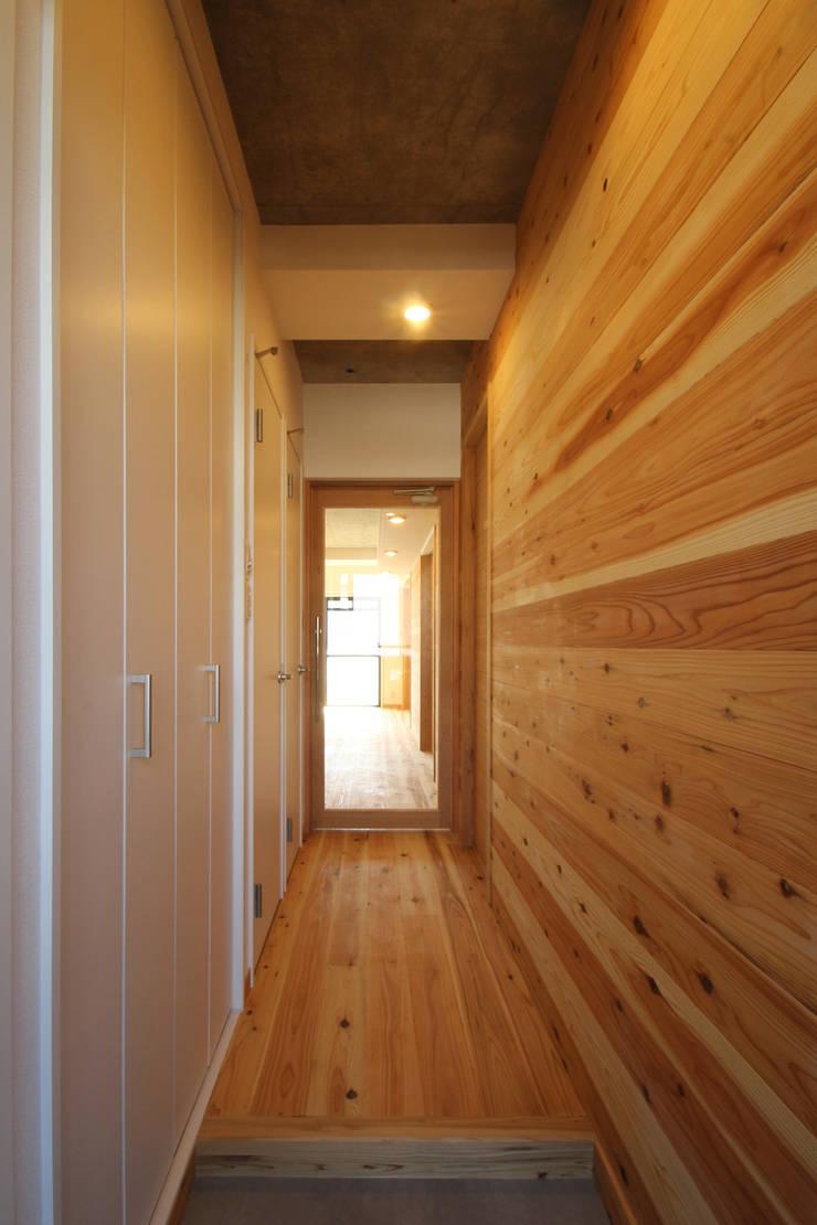 玄関からベランダまで貫く杉板貼のアクセント壁: 三浦喜世建築設計事務所が手掛けた廊下 & 玄関です。,ミニマル 木 木目調