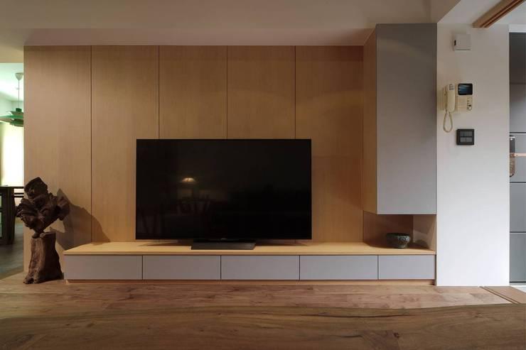 木質電視牆後是儲存空間:  牆面 by 直方設計有限公司,