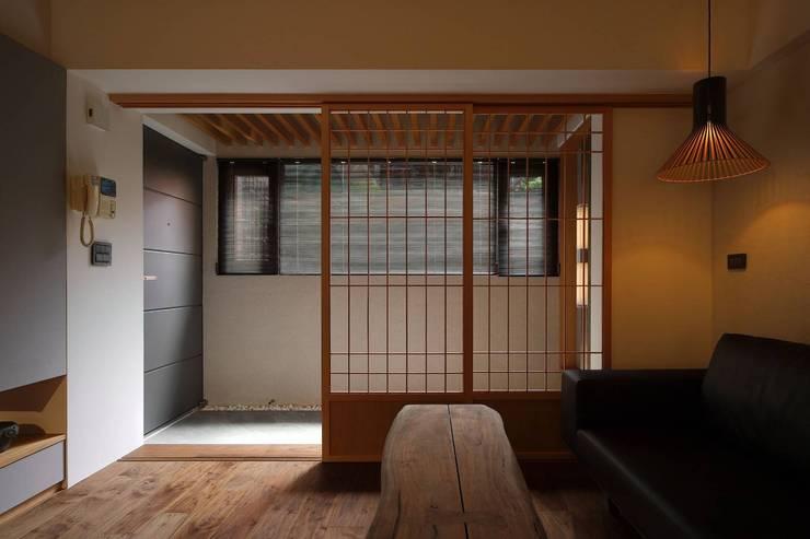 玄關使用石板地與客廳木質地板做區分:  客廳 by 直方設計有限公司,