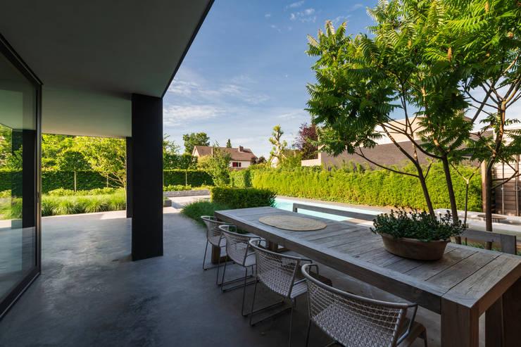Betonvloer onder overkapping:  Terras door Buro Buitenom exterieurontwerpers, Modern