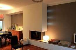 Meuble Cheminée vu depuis le séjour. Un espace multifonction proposant une cheminée, un banc intégrant des rangements, un traitement de l'espace TV / Hifi et une mise en lumière.: Salon de style de style Moderne par 3B Architecture
