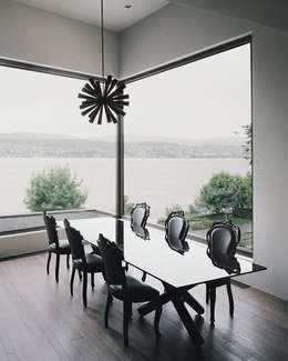 Der Essplatz mit Blick auf den verregneten See.: minimalistische Esszimmer von Lando Rossmaier Architekten AG