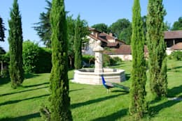 Fontaine centrale en pierre installée dans un jardin: Jardin de style de style Méditerranéen par Provence Retrouvée