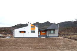 산자락에 순응하는 지붕선을 가진 집: 주택설계전문 디자인그룹 홈스타일토토의  주택