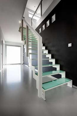 Geschilderde stalen trap met glazen treden: moderne Gang, hal & trappenhuis door YBIS