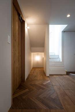 ヘリンボーンのフラットな玄関が出迎える: エンジョイワークスが手掛けた壁・フローリングです。