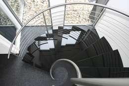 Natuurstenen RVS spiraaltrap met vrijdragende natuursteen treden: moderne Gang, hal & trappenhuis door Allstairs Trappenshowroom