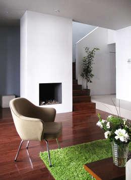 coin salon devant une fausse cheminée de bougies et escalier pour 1er étage : Salon de style de style Moderne par Studio Pan
