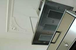 combinatie van moderne afzuigkap met klassiek plafond: moderne Keuken door TIEN+ architecten