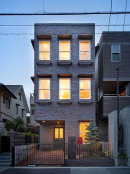 素焼きレンガの外観 夕景: atelier mが手掛けた家です。