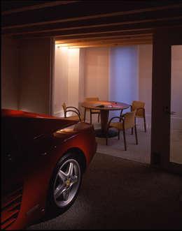 ガラススクリーン越しに趣味の部屋から車庫の中の愛車を眺められる: Guen BERTHEAU-SUZUKI  Co.,Ltd.が手掛けたガレージです。