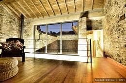 Vista da sala de estar (mezzanine) para o pátio: Salas de estar rústicas por Casa do Páteo