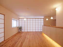 壁に収納される三枚の引き込み障子: i think一級建築設計事務所が手掛けたリビングルームです。