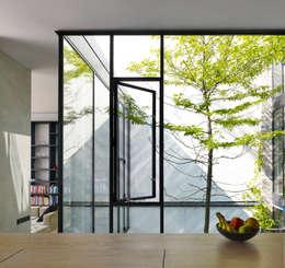 zicht vanuit de keuken naar de patio: minimalistische Huizen door office winhov