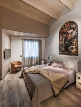 Attico mansardato: Camera da letto in stile in stile Moderno di BRANDO concept