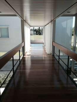 Casa Moderna: Pasillos y recibidores de estilo  por GG&A