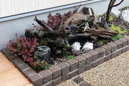 門柱から玄関までのアプローチの花壇をインパクトのある坪庭に: 有限会社 匠ガーデンが手掛けた庭です。