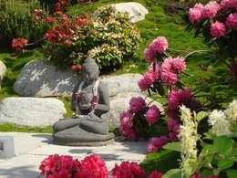 Buddha-Skulptur zwischen blühenden Rhododendren: asiatischer Garten von dirlenbach - garten mit stil
