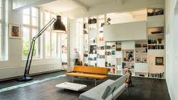 Interieur woning in school met XXL kast met taatsdeur, studie en nieuwe keuken: moderne Woonkamer door Joep van Os Architectenbureau
