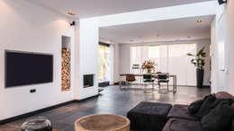 Luxe renovatie met zwevende dakopbouw, maatwerk keuken met zwevend HI-MACS keukenblok en houtfineer kastenwand: moderne Woonkamer door Joep van Os Architectenbureau