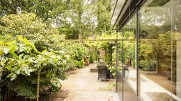 Luxe smalle aanbouw met keuken pal op het zuiden, aluminium schuifpui en lamellen zonwering: moderne Tuin door Joep van Os Architectenbureau