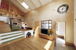 大きな吹抜けと造作本棚の家。薪ストーブに家族が集います。: 株式会社アートハウス が手掛けたリビングです。