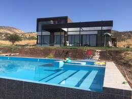 Casa en lo alto, piscina amplia mas abajo con bar incorporado: Piscinas de estilo  por Arquiespacios